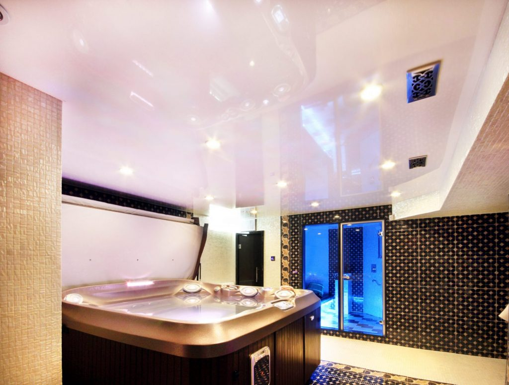 luxury hot tub room with reflective stretch ceiling in the basement