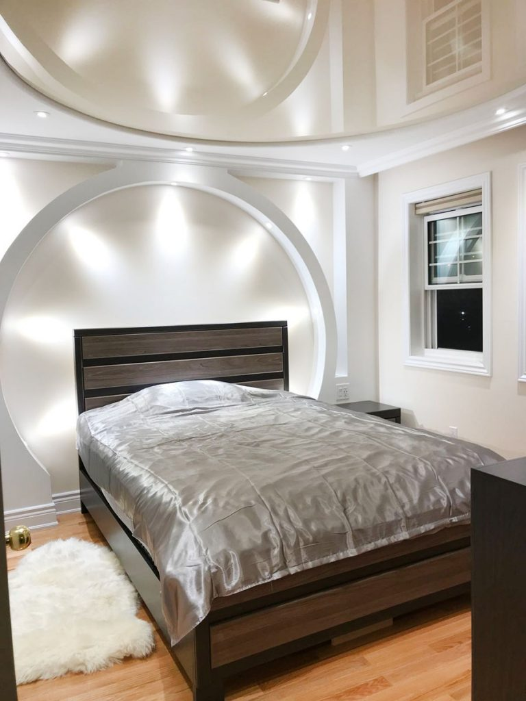 custom bedroom with high gloss stretch ceiling and back lit wall