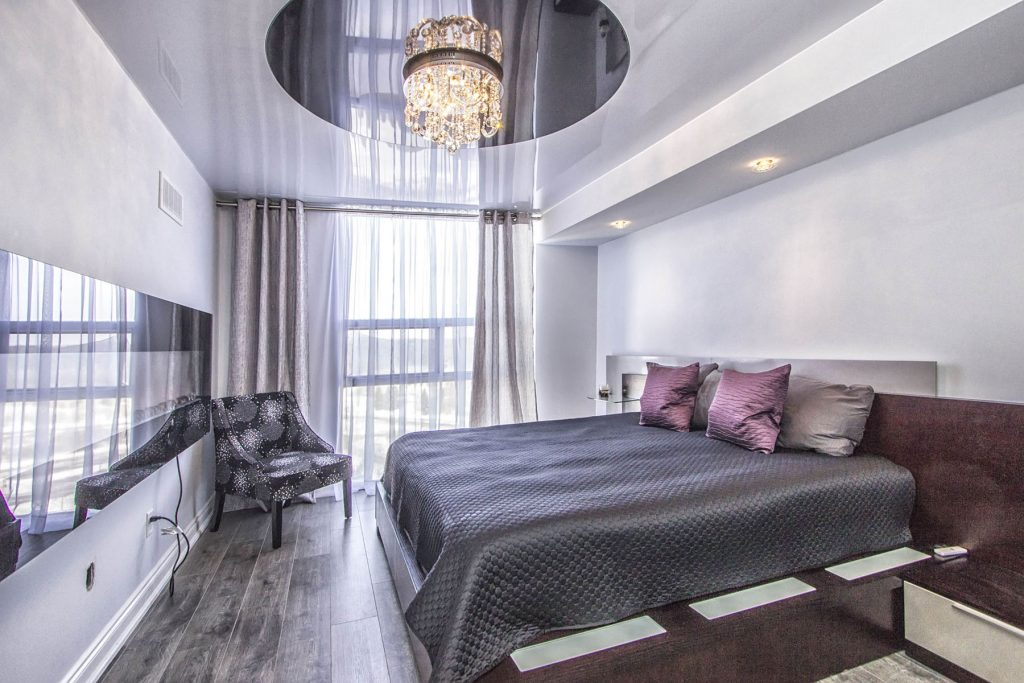 luxury bedroom with reflective multilevel ceiling
