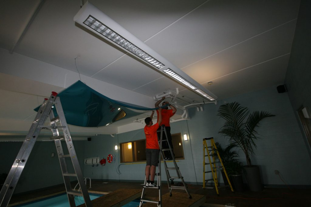 laqfoil team is hanging the modular structures in custom swimming pool area