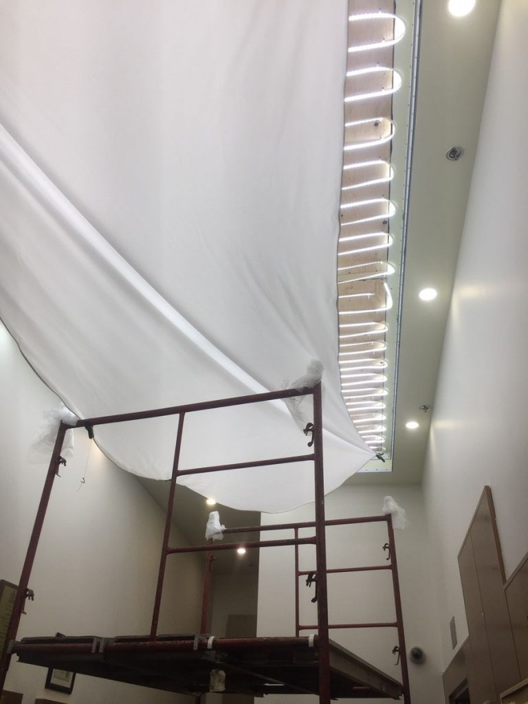 in progress of installing reflective back lit stretch ceiling by laqfoil