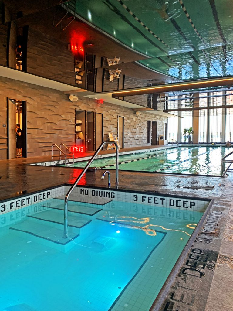 Equinox pool with black reflective stretch ceiling and orange backlit