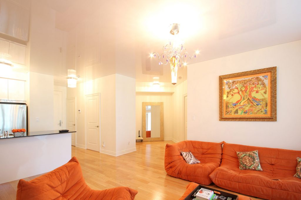 Family Rooms reflective stretch ceiling and orange sofa