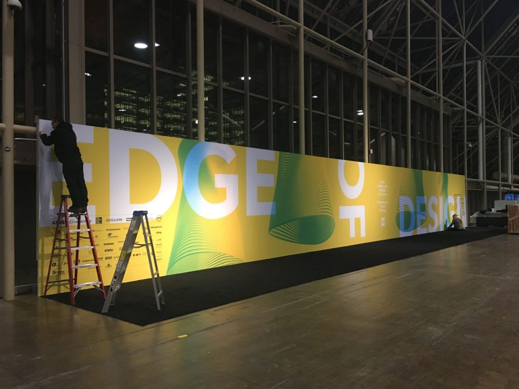 laqfoil team installing custom wall cover for IDS 2018
