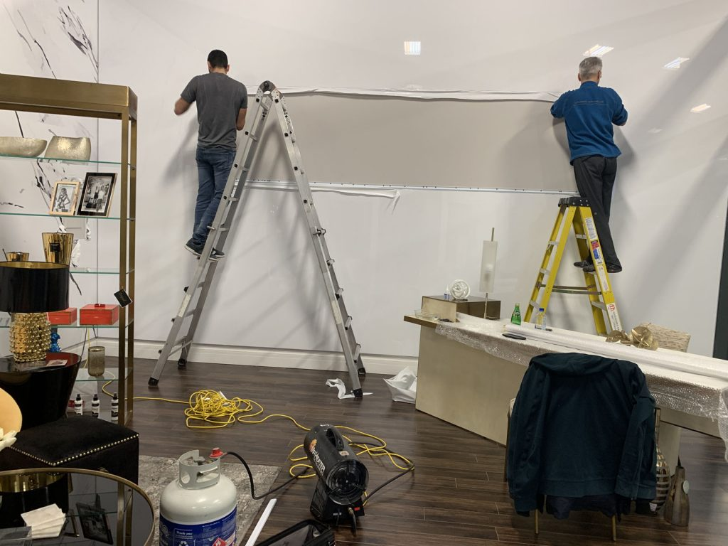 laqfoil team installing custom banner on reflective wall in showroom