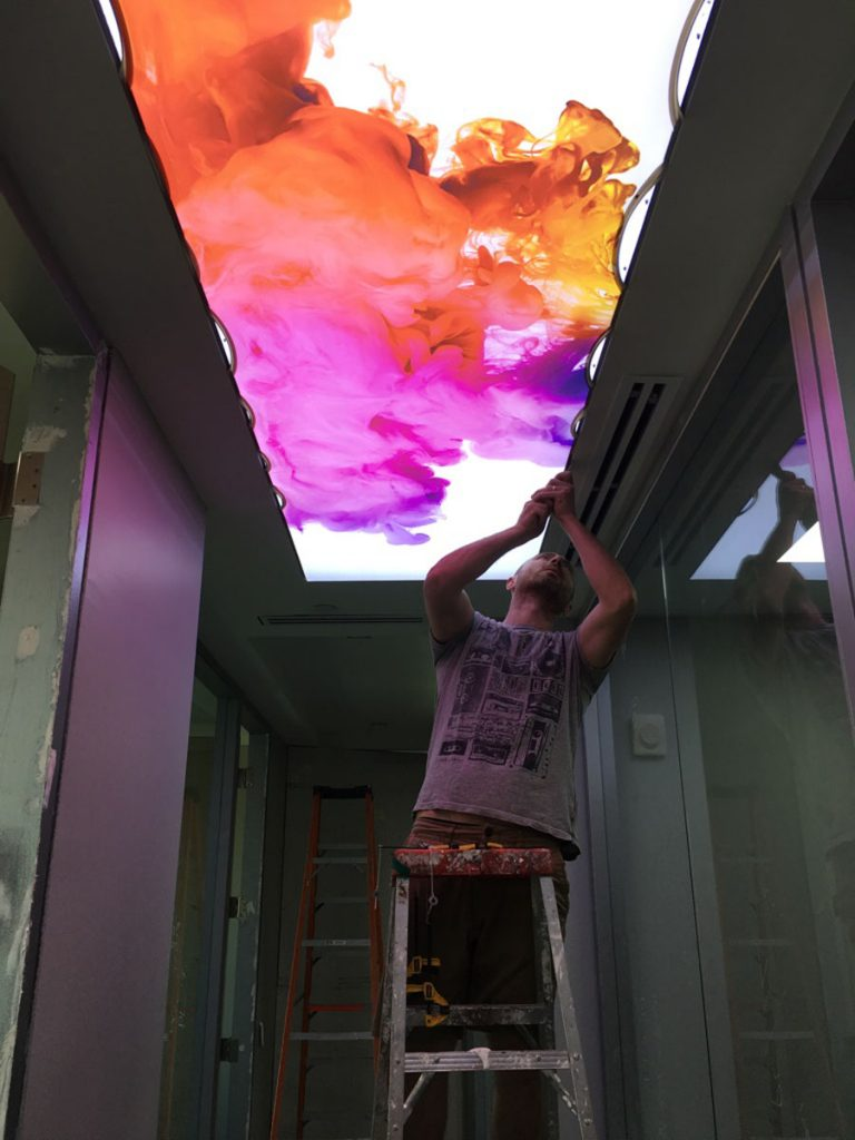 laqfoil team installing reflective printed ceiling in office hallway
