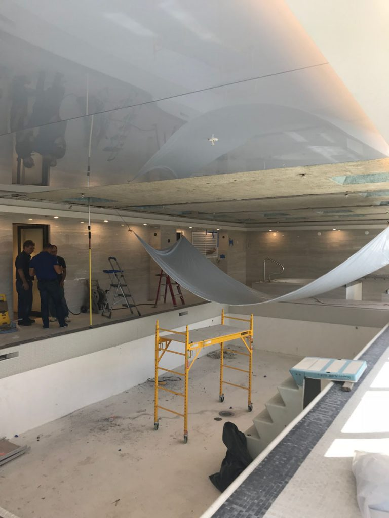 laqfoil team in progress of installing stretch ceiling fabric on luxury swimming pool