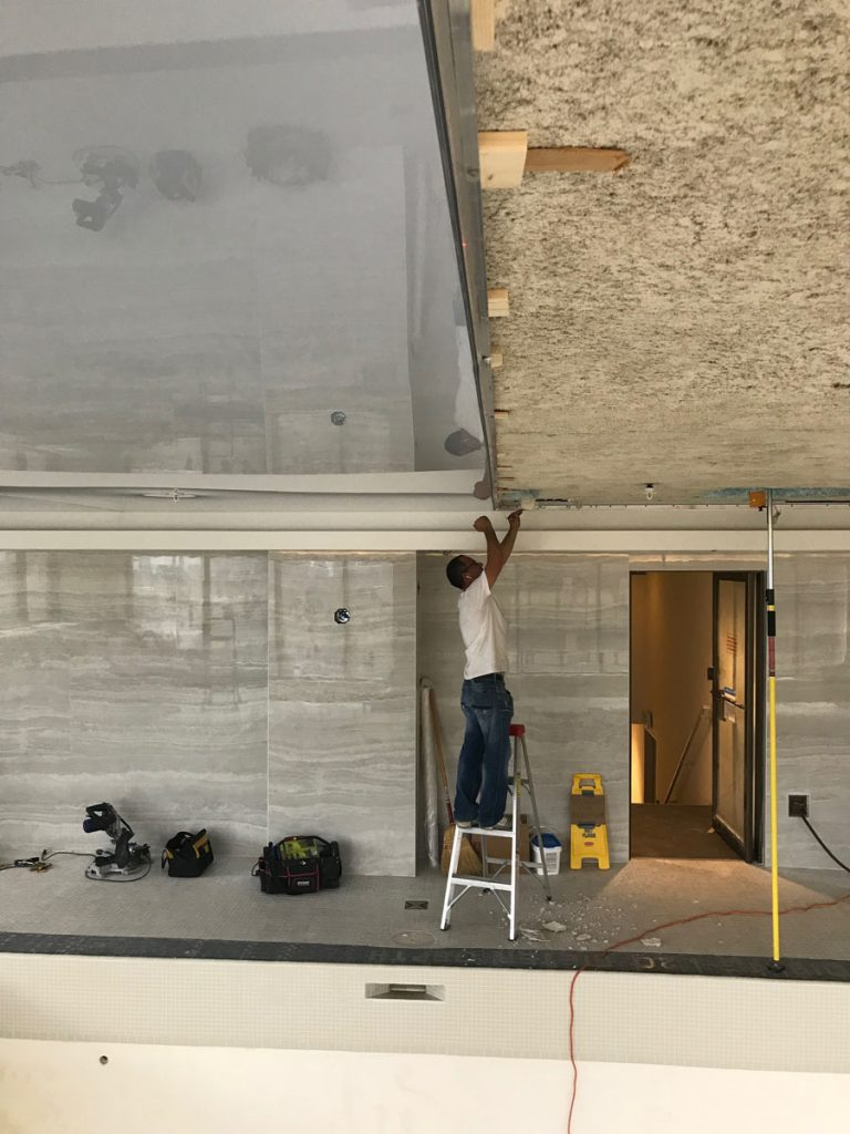 in progress of installing gloss stretch ceiling by laqfoil toronto
