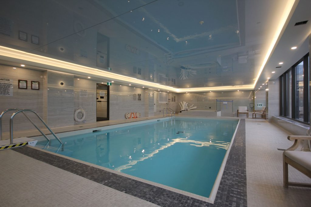 orange back lit stretch ceiling in amazing swimming pool