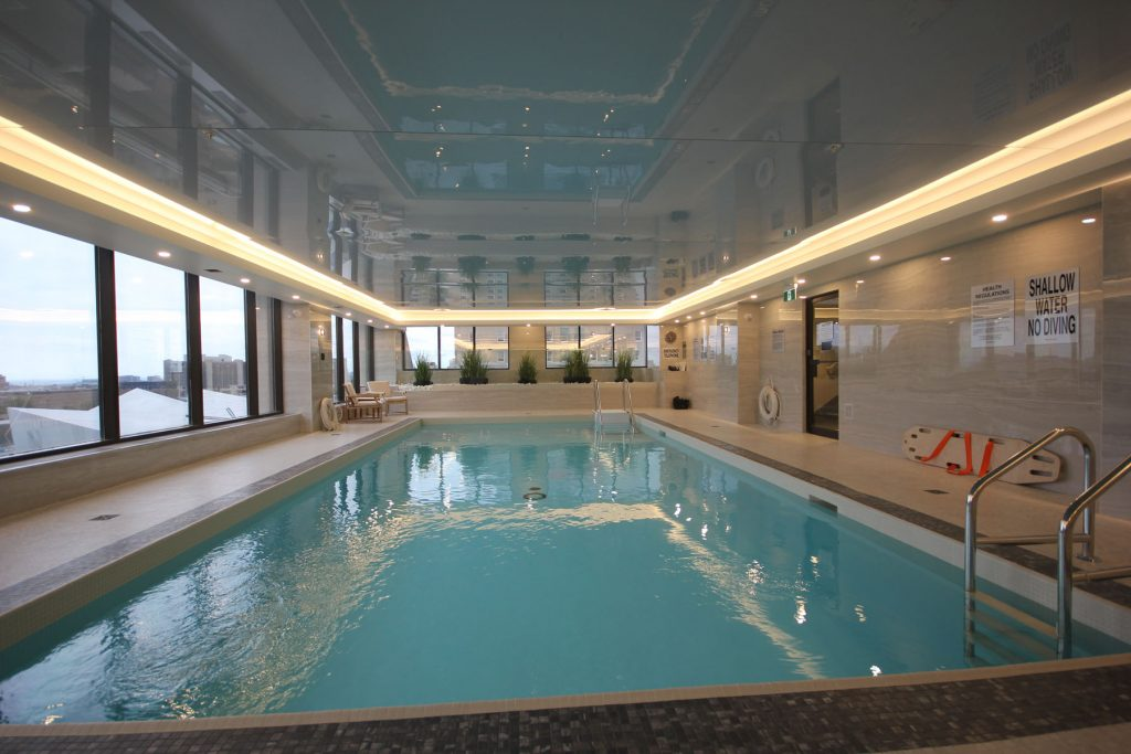 gray reflective stretch ceiling with orange back lit in custom pool