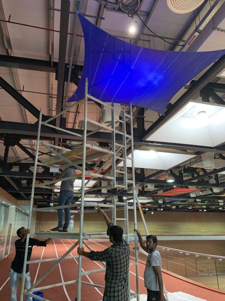 laqfoil team installing custom back lit stretch fabric modular structures