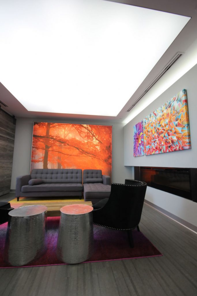back-lit white high gloss stretch ceiling and custom wall mural in luxury waiting room