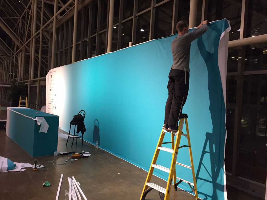 laqfoil team installing custom wall banner from stretch fabric