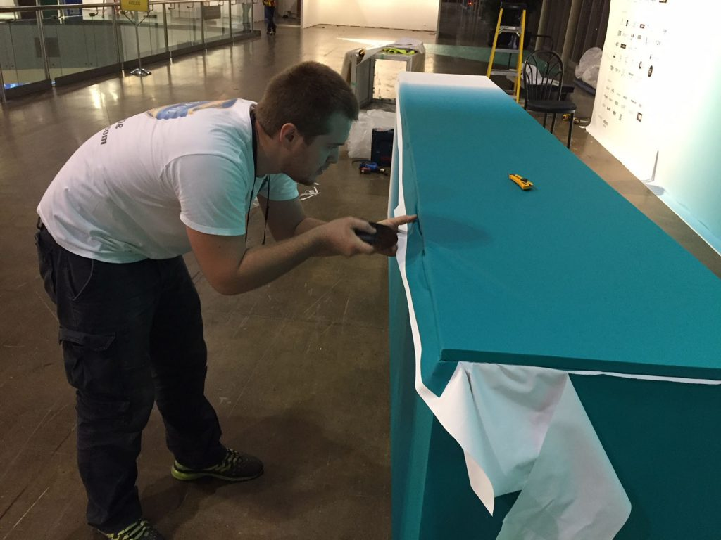 laqfoil team installing stretch fabric on reception desk
