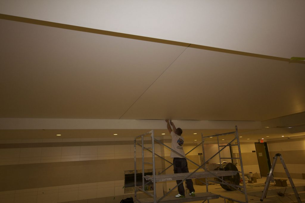 in progress of installing stretch ceiling matte in swimming pool area