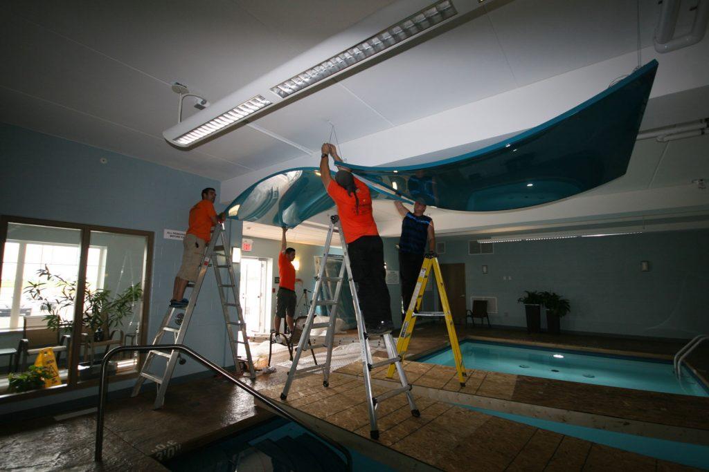 in progress of hanging blue modular structure in custom swimming pool