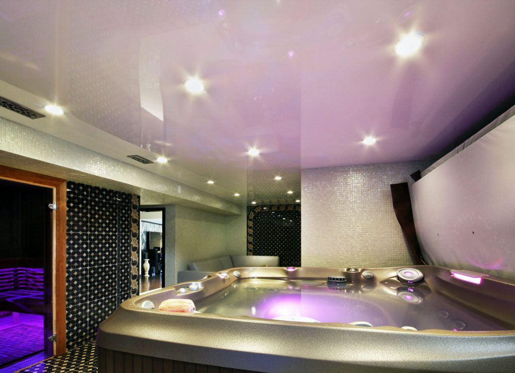 jacuzzi bathtub with luxury pink reflective stretch ceiling and potlights