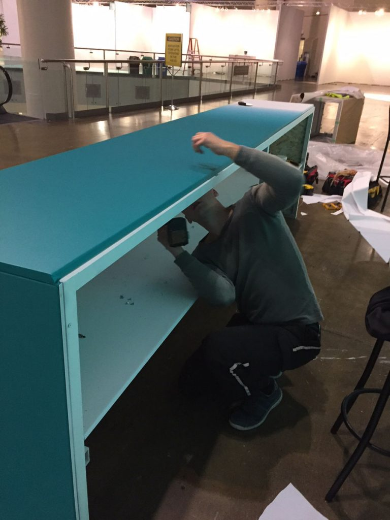 applying stretch fabric on reception desk for 2017 Toronto Art Show