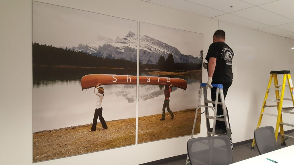 laqfoil team in progress of installing custom wall mural in rogers office
