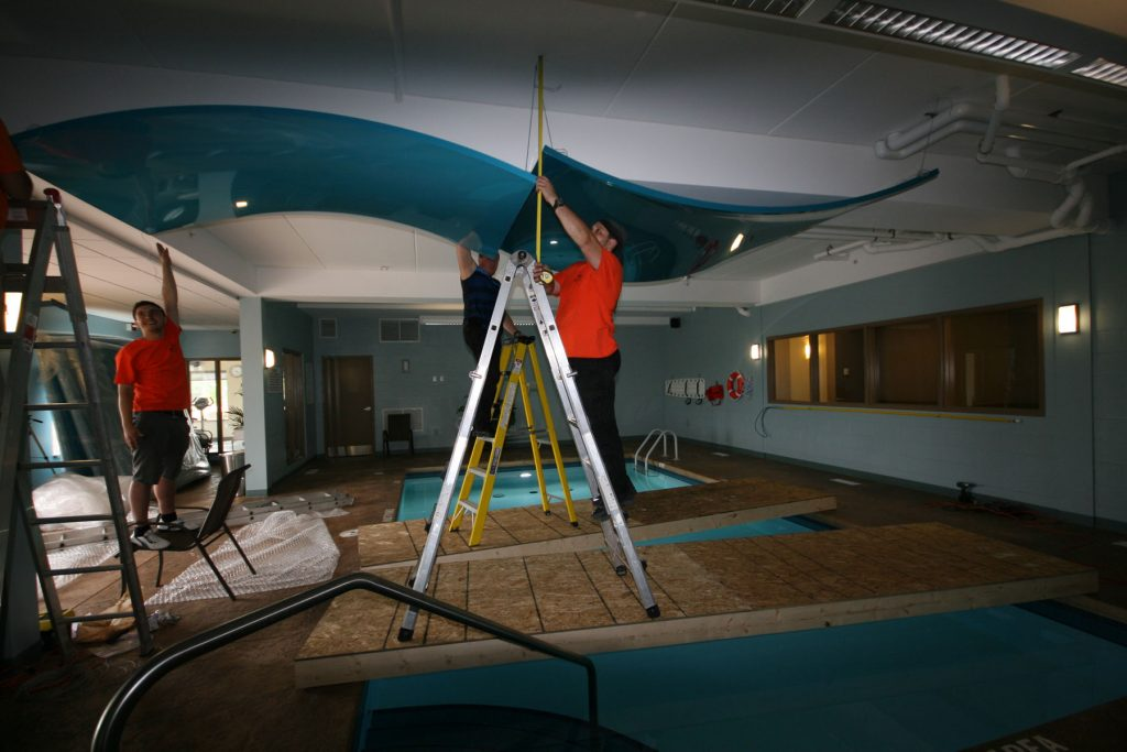 laqfoil team installing modular structures on pool ceiling