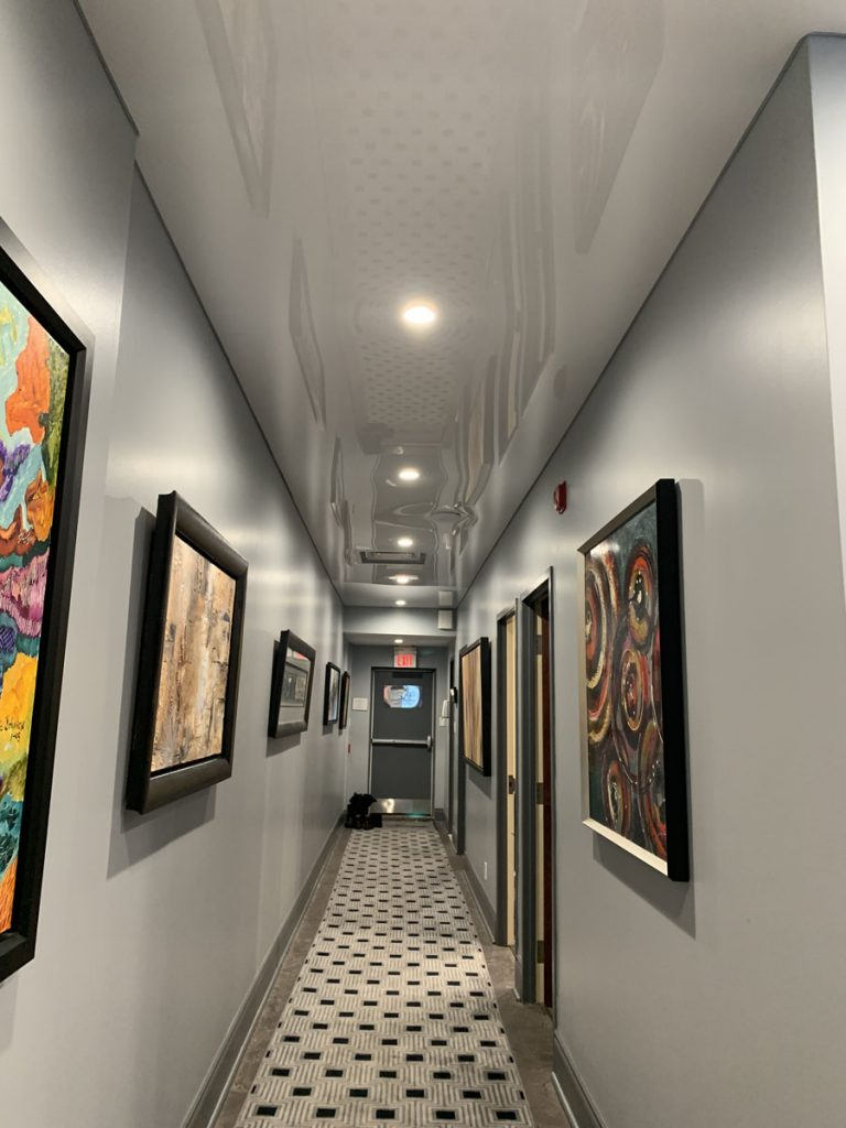 luxury office hallway with custom reflective stretch ceiling and pot lights