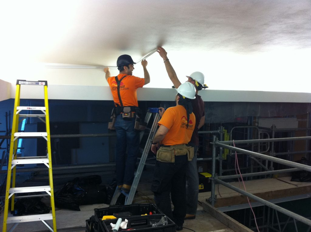 laqfoil team installing stretch fabric on back lit wall