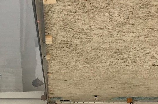 in progress of covering plain ceiling with reflective stretch ceiling