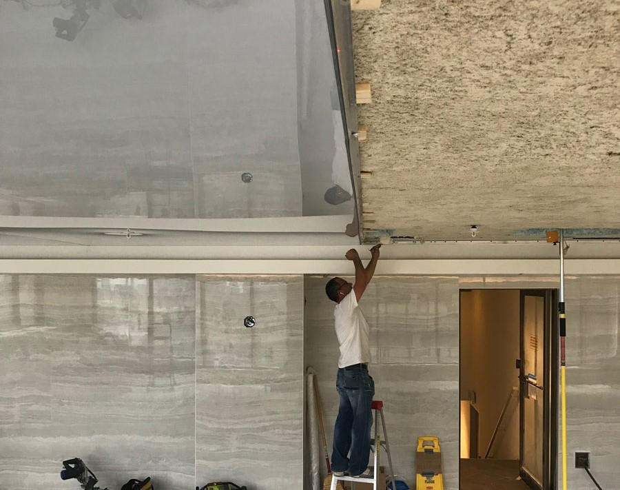in progress of installing high gloss stretch ceiling over plain ceiling in pool area